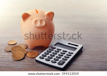 Beige piggy bank with coins and calculator on wooden background - stock photo