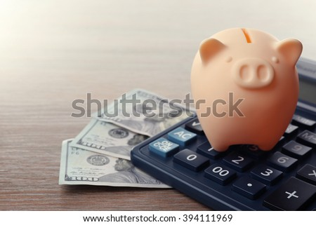 Beige piggy bank with dollar banknotes and calculator on wooden background - stock photo