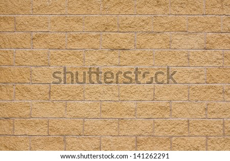 beige sandstone wall with lighter concrete grouting a good background with room for overlaid text, type, sign, poster or Graffiti. - stock photo