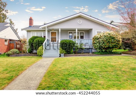 Beige siding house exterior with covered porch and trimmed bushes in front. View of soft blue staircase with narrow walkway. - stock photo