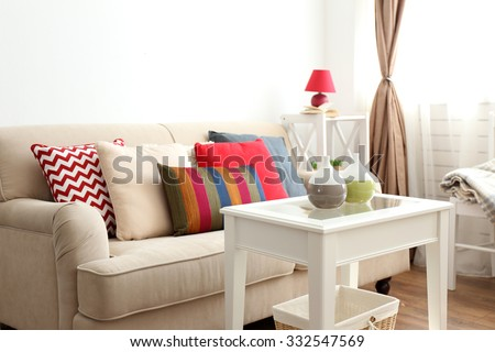 Beige sofa with beautiful pillows and decorative vases on the table in front of it in the room - stock photo