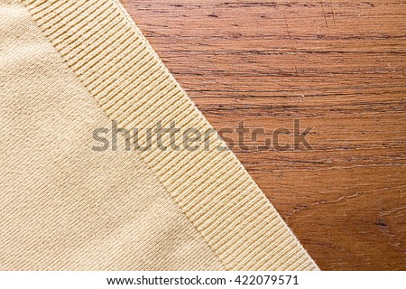 Beige sweater texture over wooden board - stock photo