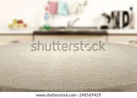 beige tablecloth and big table of free space with kitchen interior  - stock photo