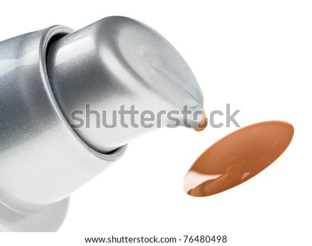 Beige tone cream (foundation) makeup drop spilled out of bottle - stock photo