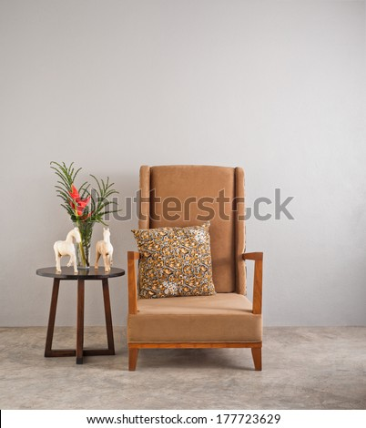 Beige upholstered chair with side table and flowers - stock photo