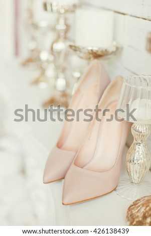 beige wedding shoes near candles - stock photo