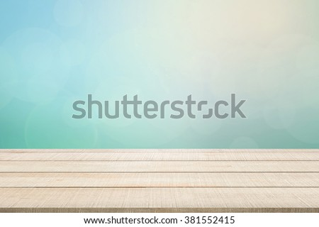 Beige wood table top panel on pastel blurred background in blue-turquoise tone with bright sunlight and flare, use for display products advertisement in natural summer concept - stock photo