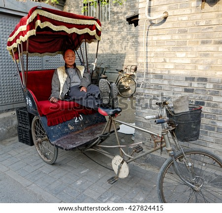 BEIJING - April 10, 2016: Chinese rickshaw driver resting in his fancy rickshaw. Tourists are warned to beware of over-charging vendors, especially who are located near tourist locations. - stock photo