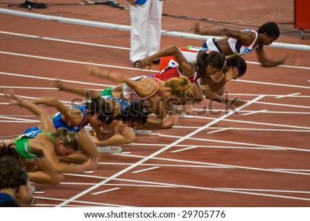 BEIJING - AUG 18: Athletes take off as the women's 100 meter sprint begins at the Summer Olympic Games.  Birds Nest Stadium August 18, 2008 Beijing, China - stock photo