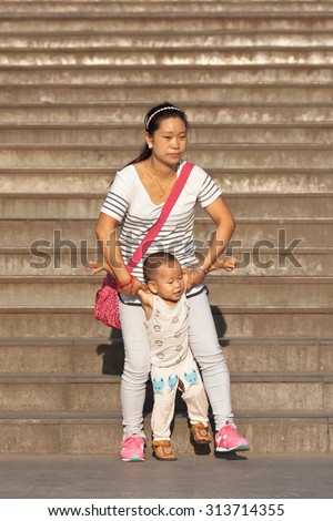 BEIJING-AUG. 27, 2015. Chinese woman with child. China's one-child policy, initiated late 1970s - early 1980s was to limit families have one child to reduce growth rate of China's enormous population. - stock photo