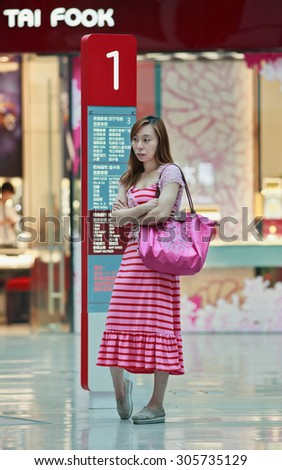 BEIJING-AUG. 2, 2015. Fashionable girl at Livat shopping mall. Owned by Inter Ikea Centre Group, its design is uniquely Scandinavian and houses over 400 renowned domestic and international brands.