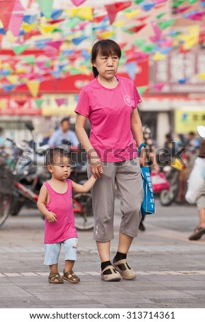 BEIJING-AUG. 5, 2015. Female elder with grandson in shopping area. In order to help their children pursue professional goals, older Chinese people often take an active role in raising grandchildren. - stock photo