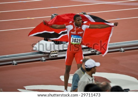 BEIJING - AUG 16: Men's 100 meter sprinter Richard Thompson takes a victory lap with American flag to celebrate his silver medal. August 16, 2008 Beijing, China - stock photo