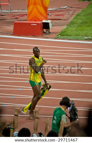 BEIJING - AUG 16: Sprinter Usain Bolt's victory lap after setting world record for men's 100 Meter sprint at the Olympics. Bolt later gains the title World's Fastest Man August 16, 2008 Beijing, China - stock photo