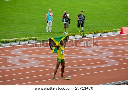 BEIJING - AUG 18: Usain Bolt celebrates holding the Jamaican flag after setting new world record  for men's 100 meter sprint at the 2008 Olympic. August 18, 2008 Beijing, China - stock photo