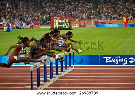 BEIJING - AUGUST 18: Athletes clear the hurdles during the women's 110M hurdles race at the Beijing Summer Olympics. August 18, 2008 Beijing, China - stock photo