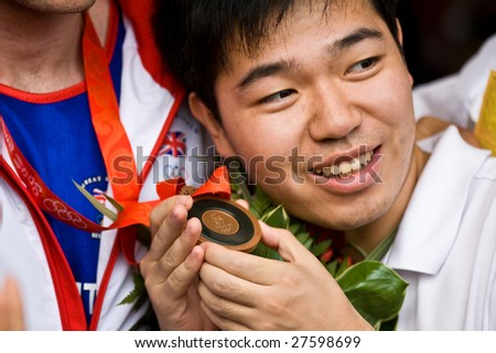 BEIJING - AUGUST  24: Chinese spectator holds Tony Jeffries Olympic bronze medal. Jeffries represents Great Brittan's in the men's light heavyweight boxing division August 24, 2008 in Beijing, China.