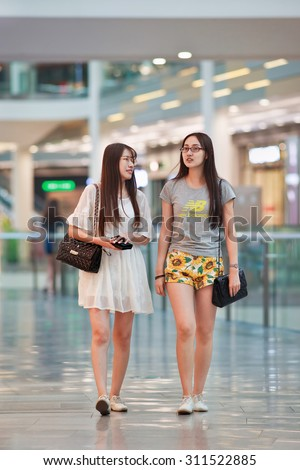 BEIJING-AUGUST 19, 2015. Girls walking in Livat shopping mall. Owned by Inter IKEA Center Group, its design is uniquely Scandinavian and houses over 400 renowned domestic and international brands. - stock photo