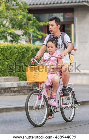 BEIJING-AUGUST 14, 2016. Man with his daughter on a rental bike at Houhai area. It is very popular among foreign tourists and often visited by expatriate community and younger generations of locals.