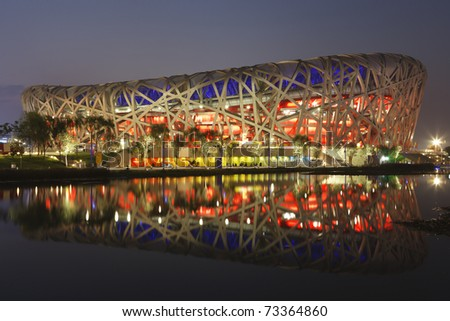 "BEIJING - AUGUST 5:  The National Stadium referred to as the ""Bird's Nest"" is lit at dusk for an opening ceremony dress rehearsal prior to the 2008 Olympic Games August 5, 2008 in Beijing, China. - stock photo"