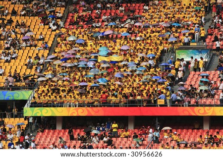 BEIJING - AUGUST 12: Umbrellas shield spectators from the sun in Workers' Stadium prior to a match between Brazil and Nigeria at the Olympic women's soccer tournament August 12, 2008 in Beijing, China - stock photo