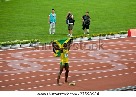 BEIJING - AUGUST 18: Usain Bolt celebrates holding the Jamaican flag after setting new world record  for men's 100 meter sprint at the 2008 Summer Olympic August 18, 2008 in Beijing, China. - stock photo