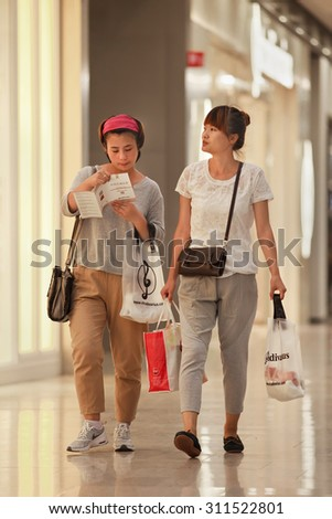 BEIJING-AUGUST 19, 2015. Young trendy woman at Livat mega mall. Owned by Inter IKEA Center Group, its unique Scandinavian design interior houses over 400 renowned domestic and international brands. - stock photo
