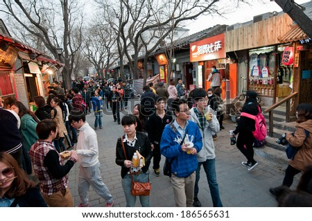 BEIJING, CHINA - APRIL 3: a lot of young Chinese people walks in Nanluoguxiang hutong - one of the most famous hutongs on April 3, 2013 in Beijing - stock photo