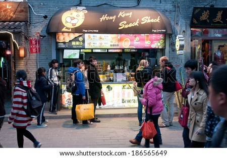 BEIJING, CHINA - APRIL 3: Chinese and foreign tourists walks in front of Hong Kong Snack Shack in Nanluoguxiang hutong - one of the most famous hutongs on April 3, 2013 in Beijing - stock photo