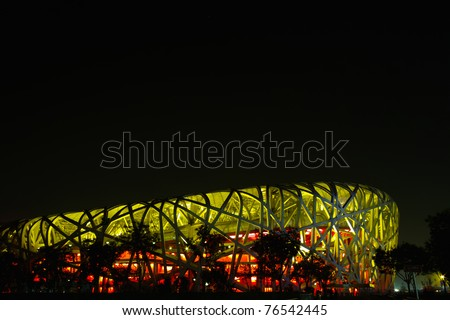 BEIJING, CHINA - APRIL 26:  The Beijing National Stadium( the Bird's Nest) lights up on April 26, 2011 in Beijing, China.As a landmark of modern China, which attracting million of tourists each year. - stock photo