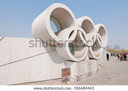 BEIJING, CHINA - APRIL 2: tourists walk in front of wall with stone Olympic rings in Olympic Green olympic park in Chaoyang District on April 2, 2013 in Beijing - stock photo