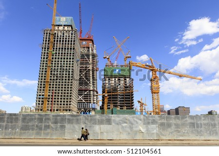 BEIJING, CHINA - APRIL 17, 2016: Unidentified people walk nearby an on-going constructions at Beijing Central Business District (CBD)
