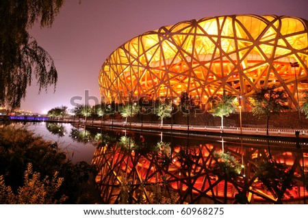 BEIJING, CHINA - AUG 8: First anniversary celebration of Olympic game on August 8, 2009 in Beijing. Stadium is light up in red with water reflection. - stock photo