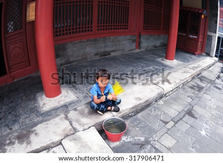 BEIJING, CHINA, AUG 29: Young child sitting in the front of a temple at the Lama Temple, Beijing, China, Aug 29, 2014 - stock photo
