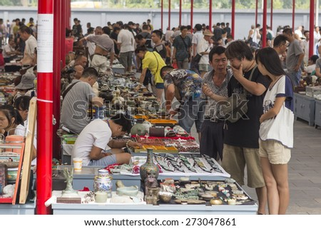 BEIJING, CHINA - AUGUST 23, 2014: People visiting and buying articles at the Panjiayuan market - stock photo