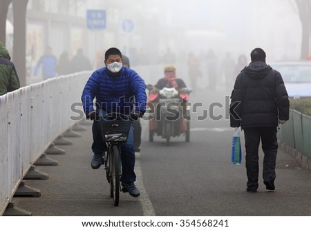 BEIJING, CHINA - DECEMBER 23, 2015: An unidentified man ride a bicycle in smog, in a foggy and hazy day. Beijing issued a red alert for air pollution on Friday, its second red alert this month.  - stock photo