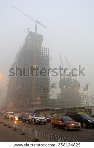 BEIJING, CHINA - DECEMBER 25, 2015: Buildings are blanketed by smog at Beijing Central Business District. More than 200 flights were canceled as heavy smog shrouded the city on Christmas Day. - stock photo