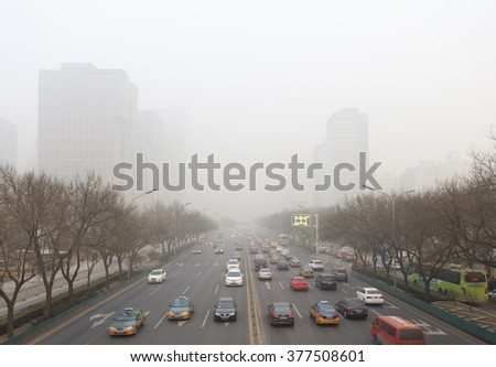 BEIJING, CHINA - DECEMBER 25, 2015: Traffic is seen at Guomao area in heavy smog. The municipality of Beijing is preparing new emissions standards for vehicles. - stock photo