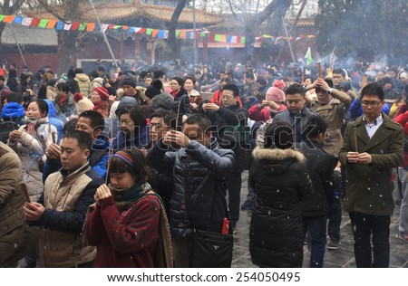 BEIJING, CHINA - FEB. 19, 2015: People pray amid a light snow at Yonghegong Lama Temple on the first day of the Chinese Lunar New Year, the year of the sheep, which started on February 19 this year.   - stock photo