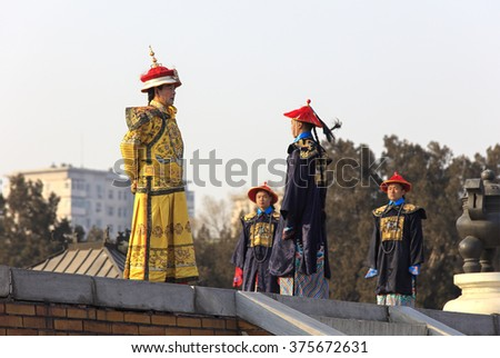 BEIJING, CHINA-FEBRUARY 10, 2016: Folk artists, dressed in traditional costumes, perform an ancient Qing Dynasty ceremony at Ditan Park. Playing the role of the Emperor is dressed in yellow costume. - stock photo