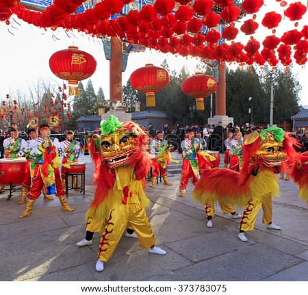 BEIJING, CHINA - FEBRUARY 8, 2016: Folk artists, dressed in traditional costumes, perform lion dance at the entrance of the Ditan Park, on the first day of the Chinese New Year, the year of the monkey - stock photo