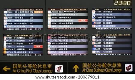 BEIJING, CHINA-JAN.23, 2014:  Monitors at Beijing Capital International Airport lists scheduled departing flights with airline logos. By March 1, 2014 it was the busiest airport in the world in 2014. - stock photo