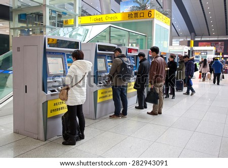 BEIJING, CHINA-JAN. 29, 2015: Passengers are seen at the self-service ticket vending machines at the Beijing South Railway station; China's railways delivered 2.357 billion passenger trips in 2014. - stock photo