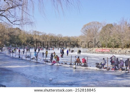 BEIJING, CHINA  15 JANUARY 2015 Students, faculty, and their families ice-skate on the frozen Weiming Lake, located in the center of the campus of Peking University (Beida, or PKU). - stock photo
