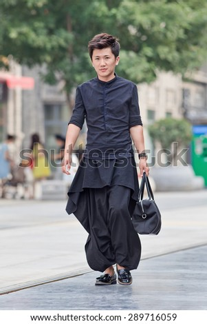 BEIJING, CHINA -JUNE 9, 2015. Fashionable young man in city center. First generation one-child policy consumers have opposite shopping habits from parents. They barely save and spend income rather on fashion. - stock photo
