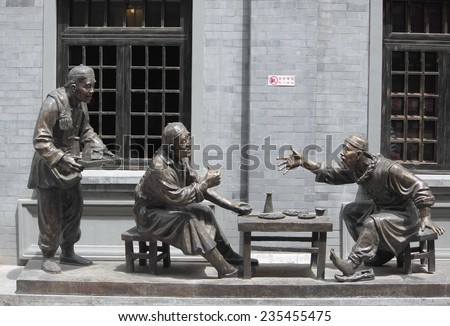 BEIJING, CHINA - JUNE 10, 2014: sculpture composition representing life of chinese people in old times on Qianmen street in Beijing, China on 10th June, 2014 - stock photo