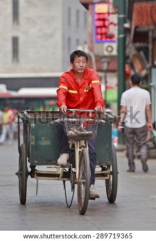 BEIJING, CHINA -JUNE 9, 2015. Street sweeper on an old tricycle. China has a gigantic army of orange dressed street cleaners do their best to clean up daily the streets in dense and over populated cities. - stock photo