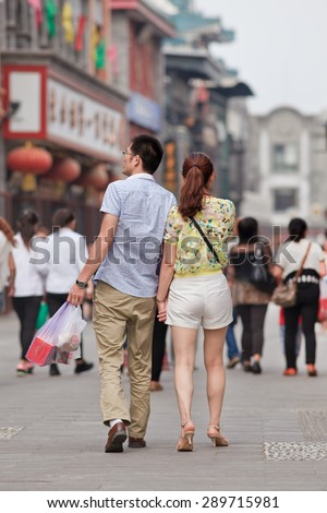 BEIJING, CHINA -JUNE 9, 2015. Young couple in city center. For decades, most urban Chinese families could have only one child. Now officials in China's capital asking young couples to have more children. - stock photo