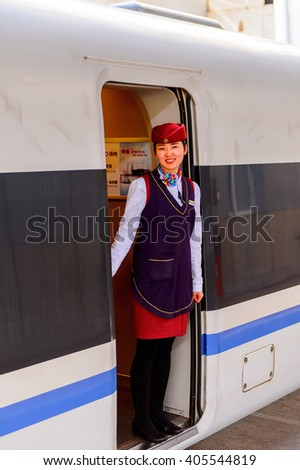 BEIJING, CHINA - MAR 27, 2016: Unientified female conductor of the China Railway High-speed train at the West Railway Station in Beijing. CRH is the high-speed rail service operated by China Railway