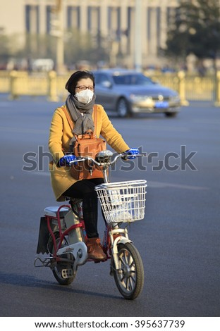 BEIJING, CHINA - MARCH 20, 2016: An unidentified woman, wearing a face mask, rides an electric bike near Tiananmen square. Beijing government's  plans to include more bike lanes for reducing city smog - stock photo
